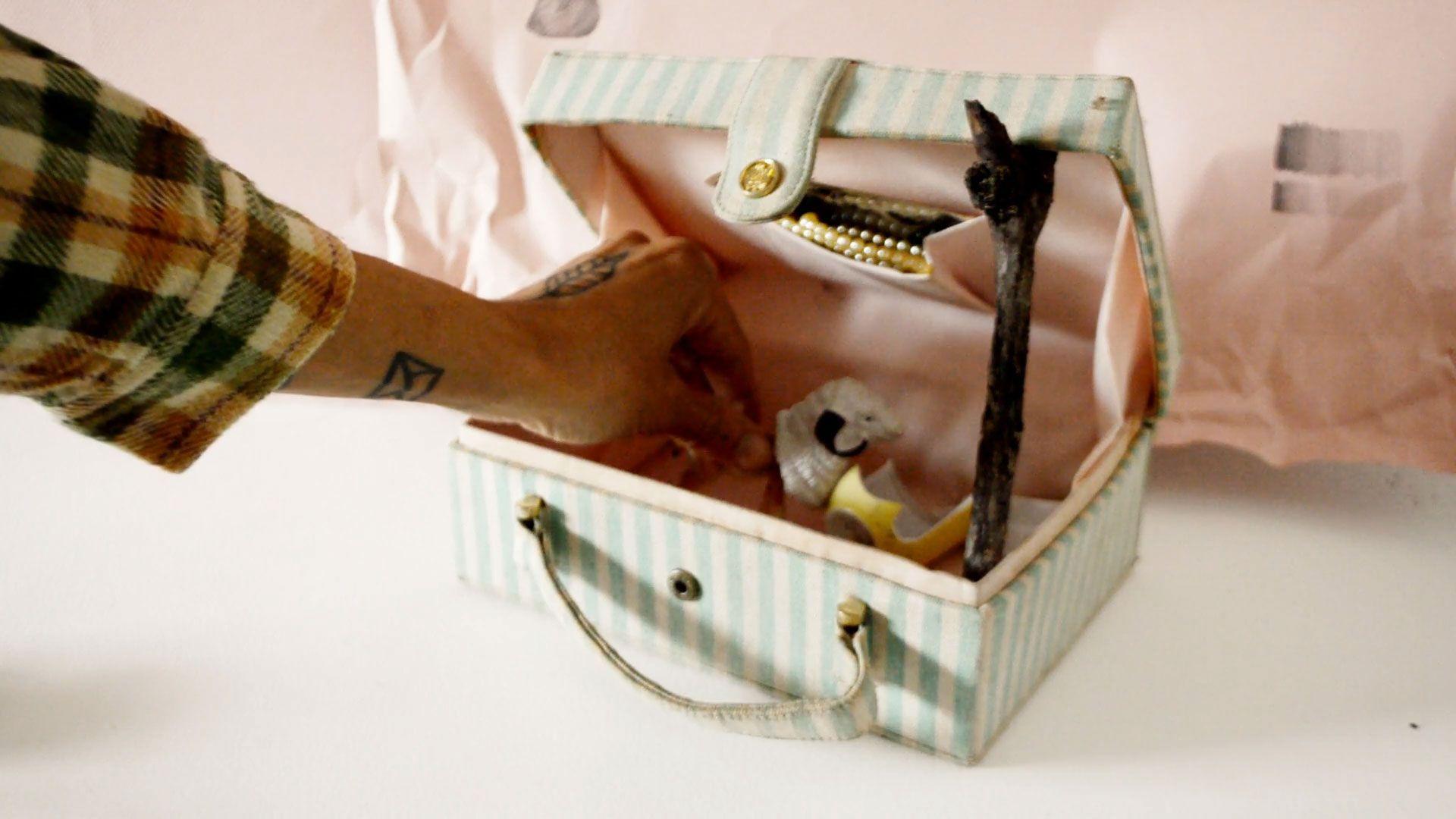 Uma pequena maleta com listras de cor azul claro e branco está posta sobre uma superfície branca, ao fundo um papel cor de rosa claro, durante o vídeo uma voz off narra uma história ao tempo que uma mão aparece inserindo elementos dentro e fora da pequena maleta.