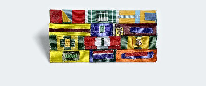 Pequeno broche que faz alusão à broches de condecoração militar, é composto de pequenas faixas de fitas de tecido coloridos, organizadas em formas geométricas diversas, coladas em placas de metal.